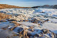 Urriðafoss waterfall frozen in winter. Sunrise golden light. South Iceland.