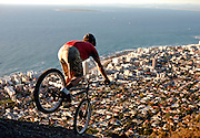 South African Trials Rider Andrew Guess finishes off the day with a practise session on Lions Head mountain, overlooking Robben Island in Cape Town. Image by Greg Beadle Portraits captured by Greg Beadle in studio and on location
