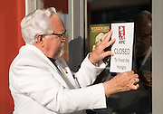 """This handout photo from KFC shows Colonel Sanders look-alike Bob Thompson putting a sign on the door Tuesday, Sept. 29, 2009 in Louisville, Ky., to show that a KFC restaurant has been converted into a """"World Hunger Relief Kitchen"""" during the lunch rush to feed residents of the local Wayside Christian Mission. KFCs across the country will be collecting donations for World Hunger Relief now through the end of October. (Photo by Brian Bohannon)"""