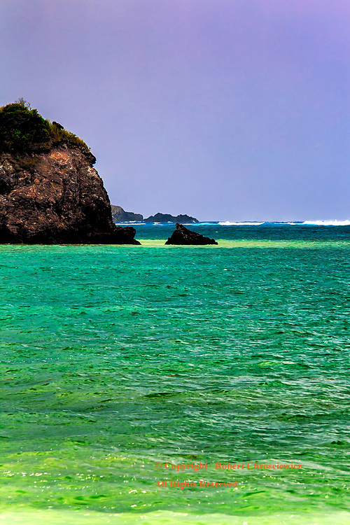 Emerald Sea: This tropical scene explodes with colour as a mauve sky hangs over a multi-coloured sea, with the waves crashing over a distant coral reef, Kuta Beach - Lombok Indonesia.