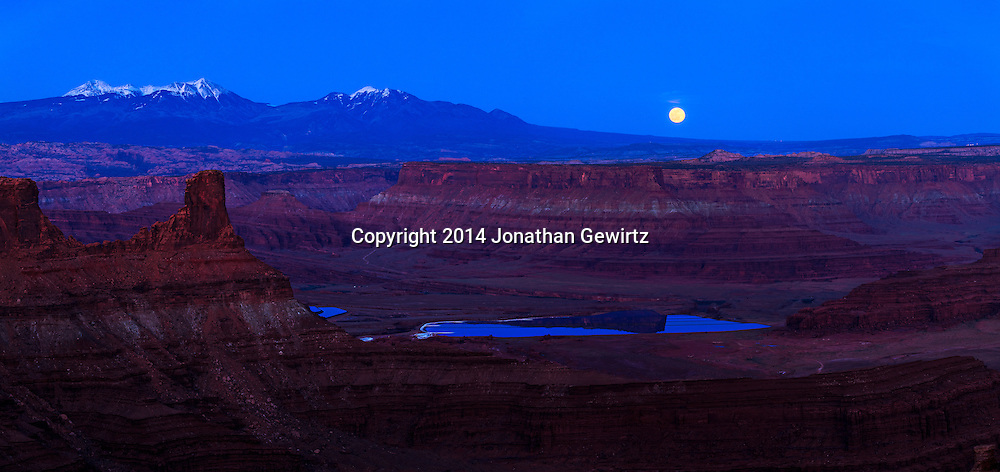 The full moon rises over canyon rims overlooking potash drying pools on the Colorado River near Moab, Utah. The La Sal Mountains are visible in the distant background.<br /> WATERMARKS WILL NOT APPEAR ON PRINTS OR LICENSED IMAGES.