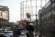 A busker plays to a large crowd on Regents Canal during the second coronavirus national lockdown on November 7th 2020 Hackney, East London, United Kingdom. The musician stopped playing before getting into trouble with the police for breaking current social distance rules. The UK Government introduced a 4 week lockdown from November 5th - December 2nd to combat the coronavirus outbreak. It is the third day of the national lockdown and restrictions mean that people are only allowed to meet outside, in pairs and only if keeping social distance. Only if they already live together or have formed a social bubble can they interact freely.
