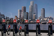 Santander-sponsored rental bikes await riders, lined up in their charging docks in front of a construction hoarding that shows the Southbank skyline, on 22nd June 2021, in London, England.