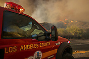 A firefighter on a fire engine watches the wildfire near Placenta Canyon Road in Santa Clarita, Calif., Sunday, July 24, 2016.(AP Photo/Ringo H.W. Chiu)
