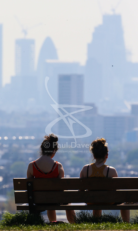 Two women enjoy the sunshine and the hazy view of the city skyline from Parliament Hill in London February 10 2018.