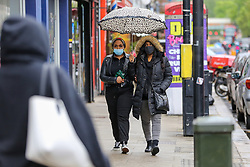 © Licensed to London News Pictures. 16/05/2021. London, UK. Women wearing face coverings shelter from light rain beneath an umbrella in north London. More rain is forecast for the South East of England this week. Photo credit: Dinendra Haria/LNP