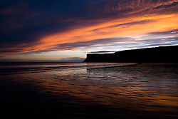 © Licensed to London News Pictures. <br /> 24/10/2014. <br /> <br /> Saltburn, United Kingdom<br /> <br /> As dawn breaks the first rays of morning light above Huntcliff in Saltburn reflect off the wet sand as the tide drops. <br /> <br /> Photo credit : Ian Forsyth/LNP