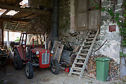 An old communist-era tractor parked under wooden structure of a traditional barn, on 20th June 2018, in Svino, Kobarid, Slovenia.