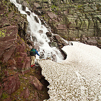 A backpacker picks a path across the bottom of a  snow-chocked waterfall near Sperry Chalet in Glacier National Park.
