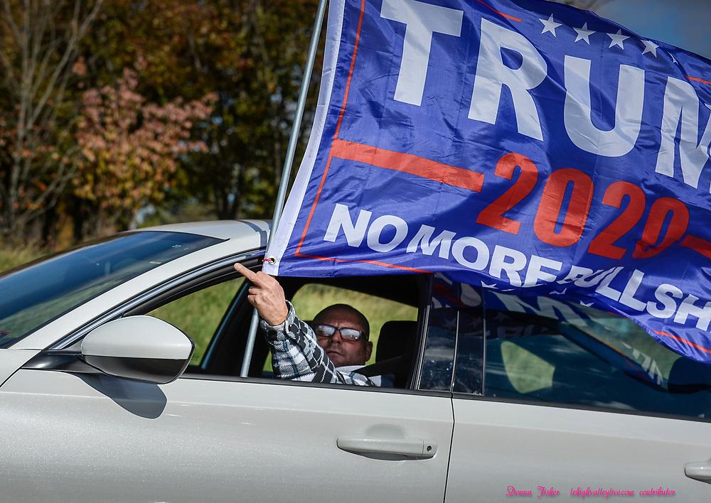 U.S. Sen. Kamala Harris, running mate of Joe Biden, speaks to supporters at Dutch Springs in Bethlehem, Pa., Monday, November 2, 2020. A Trump supporter passes the rally.