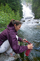 A young woman filters water while hiking in Grand Teton National Park, Jackson Hole, Wyoming.