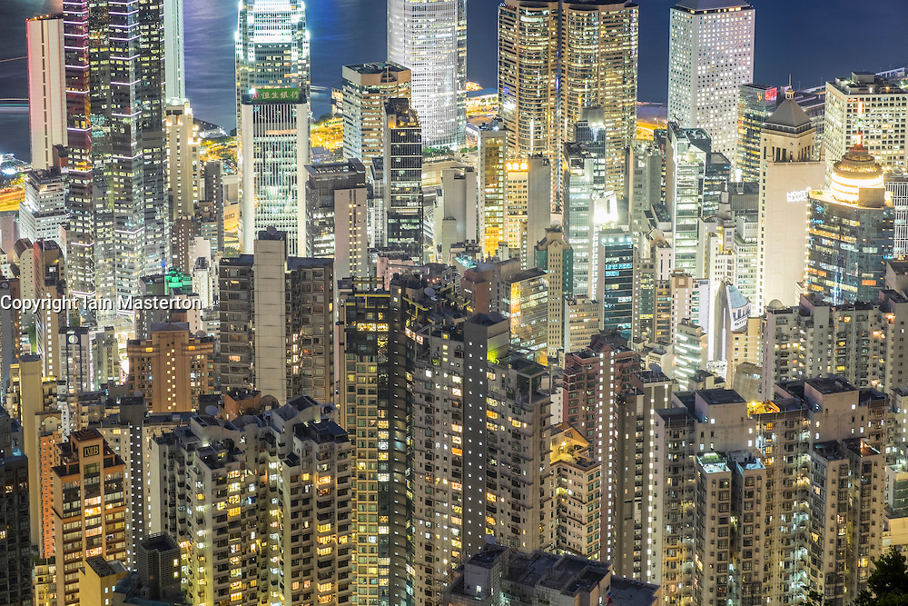Night view of many high-rise apartment buildings in dense urban district of Hong Kong China