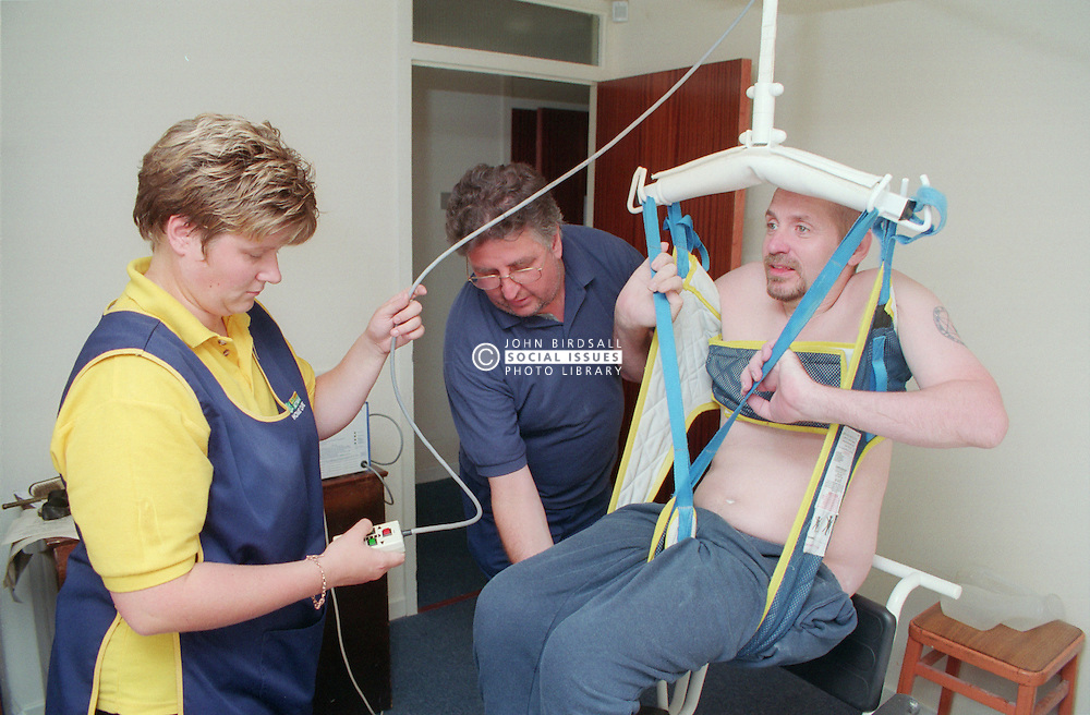 Carers using ceiling hoist to enable wheelchair to transfer into shower chair,