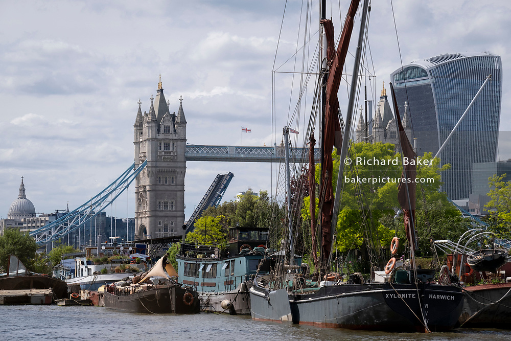 With St Paul's Cathedral, Tower Bridge and the Walkie Talkie building in the distance, barged and lighters at Tower Bridge Moorings are grouped together on the river Thames, on 11th June 2021, in London, England. Tower Bridge Moorings is the capital's only floating gardens - a sustainable way of living for a community of more than one hundred adults and children, and a shelter for wildlife on the river. Tower Bridge Moorings is the capital's only floating gardens - a sustainable way of living for a community of more than one hundred adults and children, and a shelter for wildlife on the river.