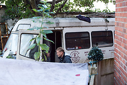 © Licensed to London News Pictures. 24/09/2019. Bristol, UK. Picture of landlord's agents onsite. Bailiffs from EAS Enforcement with the landlord and agents and police present, and being filmed by Channel 5 for television, attempt an eviction at 26 Picton Lane, Montpelier. A resident (in flat cap) can be seen on the roof of a van and building as bailiffs use a scissor lift to try and access the roof, after supporters of the resident try and block the lift from being brought to the site. Photo credit: Simon Chapman/LNP.