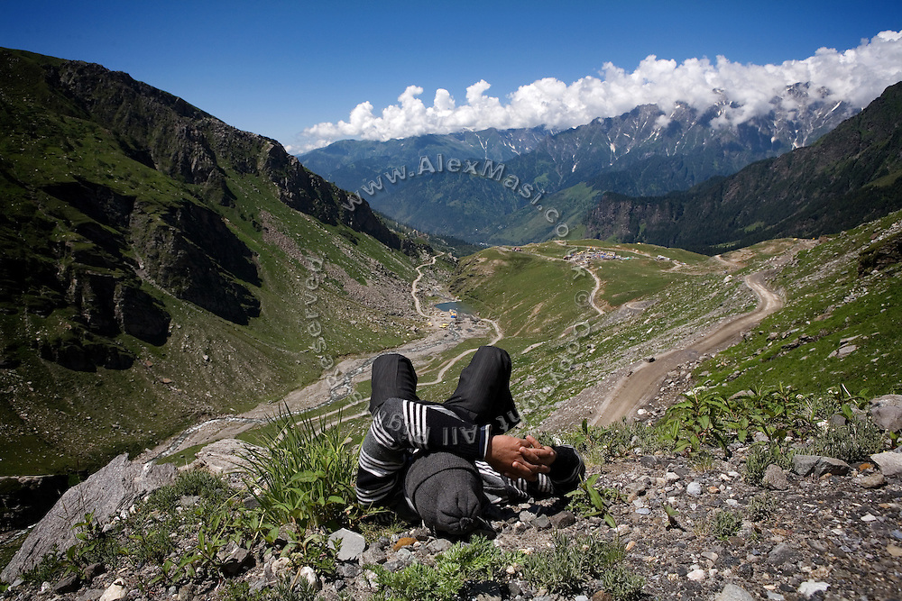 An Indian tourist is taking a break along the Leh-Manali Highway during one of the many long queues that come to create due to its steepness and narrowness. Six thousands workers are employed from East India by the Indian Army every year to maintain and strengthen the road which has become an important tourist and economic route to the north...The Leh-Manali Highway is the main road connection between the remote mountainous region of Ladhak, with capital in Leh (3300m), and Manali, HP, a famous hill station 600 km north of New Delhi. Open only four months a year, it is the second-highest motorable road in the world crossing passes up to 5300 meters. It was constructed by the Indian Army in order to develop the surrounding areas as well as monitoring the nearby borders with Kashmir and China. Due to its beauty and increased accessibility, the road to Leh and Ladhak has recently become a must-see destination for local and international tourists leaving the scorching Indian plains..