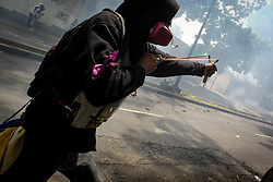 The opposition supporter throws a stone at the anti-riot police in a demonstration against Venezuelan President Nicolas Maduro this May 1, 2017.