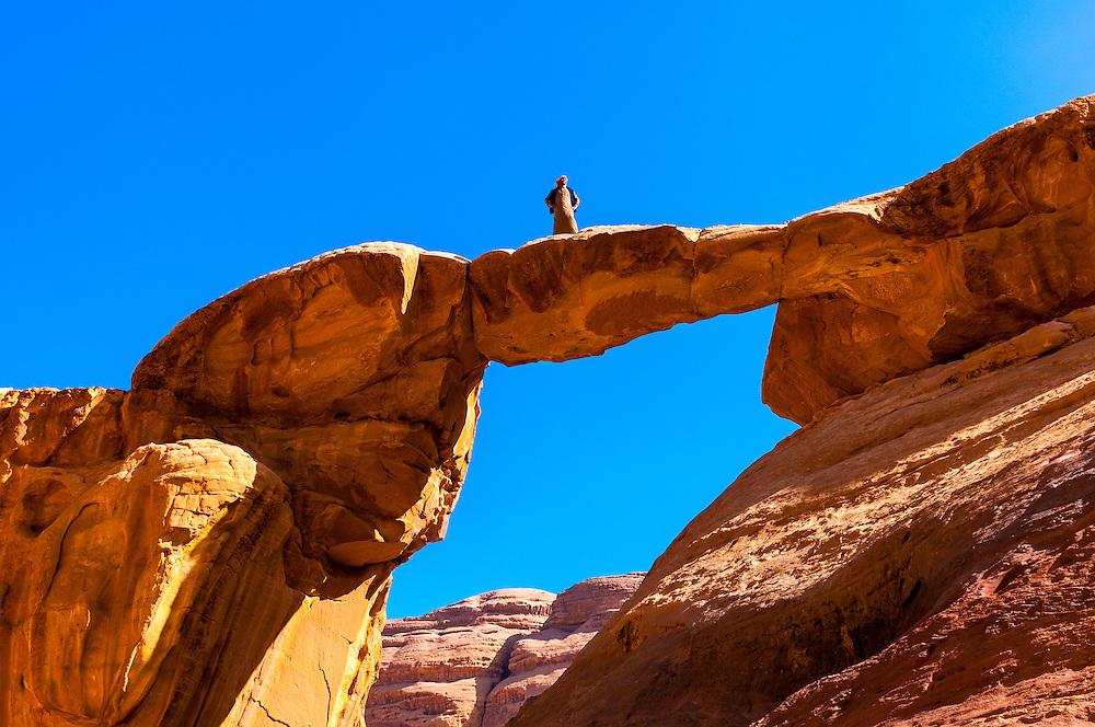 Bedouin man atop the Burdah Rock Bridge, Arabian Desert, Wadi Rum, Jordan.