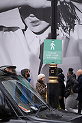 On the day that the UK government eased Covid restrictions to allow non-essential businesses such as shops, pubs, bars, gyms and hairdressers to re-open, shoppers on Oxford Street pass-by a large fashion retail ad, on 12th April 2021, in London, England.