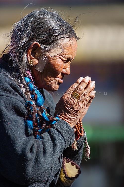 Praying woman at Barkhor Square, Lhasa, Tibet, China. Photo ©robertvansluis.com