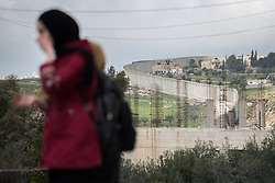 26 February 2020, Abu Dis, Palestine: A woman walks towards the Al-Quds ('Jerusalem') University in Abu Dis, with the separation wall mounted by the Israeli authorities in the background.