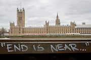 """Graffiti quoting that The """"End Is Near"""", written on a bench overlooking the Houses of Parliament across the river Thames in Westminster, on 27th March 2019, in London, England"""