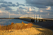 Nederland, Zeeland, Oosterschelde, 03-12-2008; Zealand, storm surge barrier in Oosterschelde (East Scheldt), between Islands of Schouwen-Duiveland and Noord-Beveland; North Sea on this side of the barrier; the sand on the beach in the forground has been suplemented (in order to protect the coast); on the new small dunes marram grass (beach-grass) has been planted; under normal circumstances the barrier is open to allow for the tide to enter / exit; in case of high tides in combination with storm, the slides are closed; Oosterscheldekering gezien van het strand van Noord-Beveland naar Schouwen-Duiveland, aan deze zijde van de kering de Noordzee; in de voorgond neiouw zand op het strand, resultaat van zandsuppletie, op de jonge duintjes is helmgras geplant; <br /> foto/photo  Siebe Swart