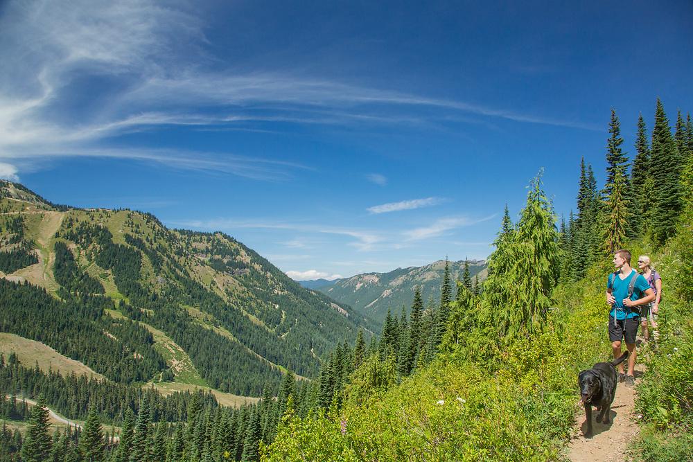 United States, Washington, Crystal Mountain, woman, teenage boy and black dog on hiking trail.  MR