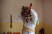Un hombre se coloca una máscara de tigre y se dirigirse al lugar donde se enfrentará a otros tigres durante el ritual de petición de lluvias.