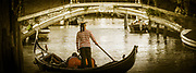 Toned photo of a gondolier with the traditional striped shirt and hat standing in a gondola approaching a bridge  in a Venice canal