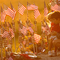 SHANKSVILLE, PA - SEPTEMBER 11:  A mother holds her daughter as the sunsets behind them at the Temporary Memorial for the crash of Flight 93 on September 11, 2004 near Shankville, Pennsylvania on the third year anniversary on the terrorist attacks of 911. (Photo by Archie Carpenter/Getty Images)