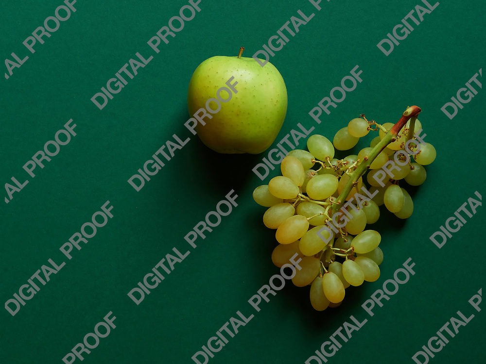 Green apple and bunch of green grapes isolated in studio with a green background viewed from above