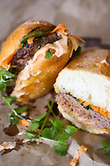 A spicy lamb bahn-mi burger with cilantro, spicy aoli, jalepenos, and pickled carrots.