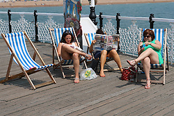 © Licensed to London News Pictures. 12/07/2014. Brighton, UK. People sunbathing on Brighton East Pier. With temperatures around the 23C down the South Coast thousands of people taking a weekend away down on the beach. Photo credit : Hugo Michiels/LNP