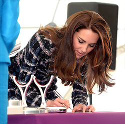 The Duchess of Cambridge signs a a photo for a time caspsule as she visits the National Graphene Research Institute during a day of engagements in Manchester.