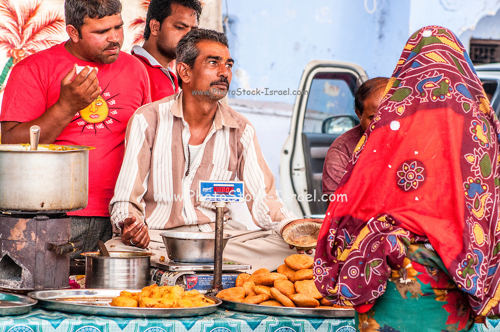 Street vendor sells Indian food off a street stall. Photographed in Pushkar, India