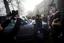 © Licensed to London News Pictures. 28/12/2016. London, UK. A woman poses for a photograph next to tributes left on the bonnet of George Michaels car outside his London home in Highgate, North London. Pop superstar George Michael died on Christmas day at his Oxfordshire home on the River Thames aged 53. Photo credit: Ben Cawthra/LNP