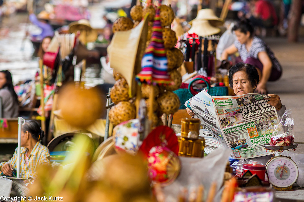 17 JANUARY 2013 - DAMNOEN SADUAK, RATCHABURI, THAILAND: A marker vendor reads her newspaper in the Damnoen Saduak (also spelled Damnoensaduak) floating market. The floating market in Damnoen Saduak is one of the best known tourist attractions in Thailand. The canal was dug in the 1860's to connect to provincial towns south of Bangkok. At the time it was the straightest, longest canal in Thailand. Thousands of tourists, both foreign and Thai, visit Damnoen Saduak to see the floating market and experience canal life.     PHOTO BY JACK KURTZ
