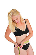Eating disorder and body image young woman measures her hip with a tape measure. She may be keeping track of weight loss during a diet but compulsive body analysis may be a symptom of a body image disorder such as anorexia nervosa. Model released