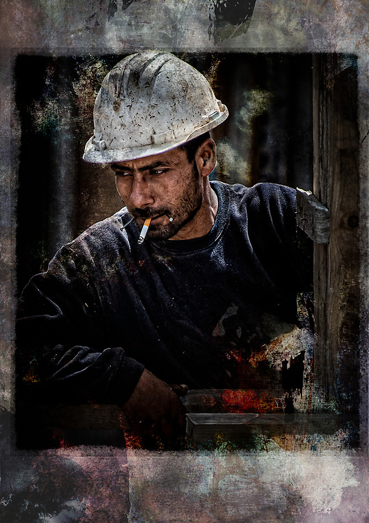 Gritty portrait of hardhat construction worker 'smoking' nails