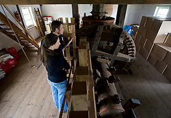 """Jette Hannaart, 28, of Delft, NL and Corne Van Kempen, 42, of Rotterdam, NL, take a tour of the De Ster Snuff and Spice mill in Rotterdam, The Netherlands. The are looking at the camshaft which is 40 cm in diameter and 11 meters long, drives the edge mill and powers the giant blades in the chopping room below. The Wallower on the main shaft, (the small horizontal wheel with orange bands) drives the camshaft when the wheel is engaged and connected to the large vertically mounted camshaft wheel. Hannaart, said """"we were just walking around and saw the sign that the mill was open for tours, what a nice surprise!"""" (Photo © Jock Fistick)"""