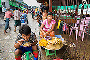 09 JUNE 2014 - YANGON, MYANMAR: A worker eats his noodles near a snack vendor in the San Pya Fish Market (also spelled Sanpya). San Pya Fish Market in Yangon is one of the largest wholesale fish markets in Yangon. The market is busiest in early in the morning, from before dawn until about 10AM.    PHOTO BY JACK KURTZ