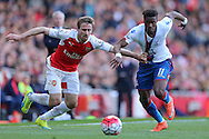 Nacho Monreal of Arsenal and Wilfried Zaha of Crystal Palace run for the ball. Barclays Premier league match, Arsenal v Crystal Palace at the Emirates Stadium in London on Sunday 17th April 2016.<br /> pic by John Patrick Fletcher, Andrew Orchard sports photography.