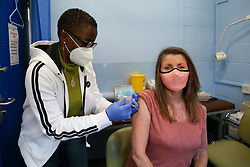© Licensed to London News Pictures. 11/04/2021. London, UK. A NHS staff member administers the second dose of the Oxford AstraZeneca Covid-19 vaccine to a woman at a vaccination centre in Haringey, north London. Over 30 million people have received a first dose and just under 7 million people have received a second dose of the Covid-19 vaccine in the UK. <br /> <br /> ***Permission Granted***<br /> <br /> Photo credit: Dinendra Haria/LNP