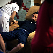 """Jeans factory boss Mr Yang enjoys a massage in Zhongshan city, China. .This picture is part of a photo and text story on blue jeans production in China by Justin Jin. .China, the """"factory of the world"""", is now also the major producer for blue jeans. To meet production demand, thousands of workers sweat through the night scrubbing, spraying and tearing trousers to create their rugged look. .At dawn, workers bundle the garment off to another factory for packaging and shipping around the world..The workers are among the 200 million migrant labourers criss-crossing China.looking for a better life, at the same time building their country into a.mighty industrial power."""