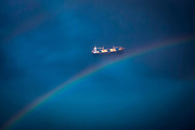 A rainbow over a cargo ship sailing across the Indian Ocean travelling between Dar-Es-Salaam and Zanzibar taken from an aeroplane.