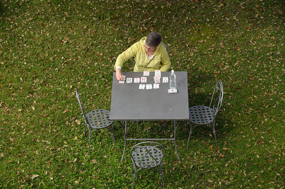 Woman playing solitaire at a table outdoors.