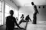 NAIROBI, KENYA - MARCH 18, 2010: In Jericho, a district on the outskirts of Nairobi, athletes with the Kibera Olympic Boxing Club await the announcement of their opponents as the ring is assembled.<br /> <br /> Within Kenya's progressive youth culture is the Kibera Olympic Boxing Club, a group of low-income adolescents from the slum whose leader uses boxing as a way to engage with idle youth. The group's ethnic diversity is remarkable given Kenya's 2008 post-election violence in which people from several tribes were forced violently out of slums. Together, these boxers represent a nascent trend of cross-tribe brotherhood in a healing nation.
