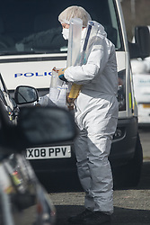 © Licensed to London News Pictures . 26/03/2015 . Manchester , UK . A forensic examiner removes a baseball bat in a plastic tube from the house . Forensic scenes of crime examiners search a house on Chain Road , Blackley , North Manchester as police in Manchester say they are investigating historical crimes . Approximately a dozen police and forensic examiners and eight police vehicles are deployed at the scene . Photo credit : Joel Goodman/LNP