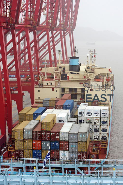ZHEJIANG PROVINCE, CHINA - March 22: A Cosco container ship waits to be loaded with Cosco containers in Ningbo port on March 22, 2006 in Zhejiang province, China. Cosco stands for China Ocean Shipping Co. (Photo by Servais Mont/Getty Images)